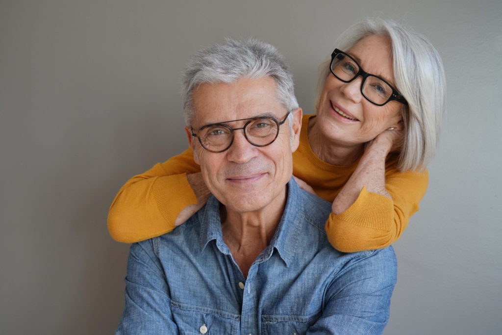 senior couple smiling and wearing glasses